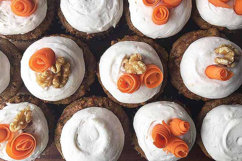 A top down view of paleo carrot cupcakes with white frosting, a walnut on top and thinly sliced carrots arranged in a swirl.