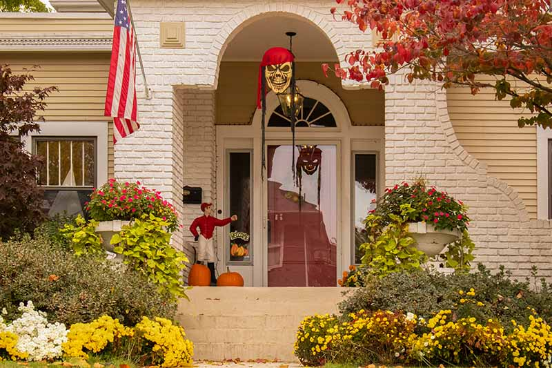A view towards a front porch of a white brick and weatherboard house. To either side of the steps are shrubs and flowers in yellow, red, and white. In the enclosed porch is a statue of a man wearing a red shirt and white breeches, with two pumpkins at his feet. In the center of the frame is a halloween decoration hanging from the arched entranceway. An American flag hangs on the left of the doorway.