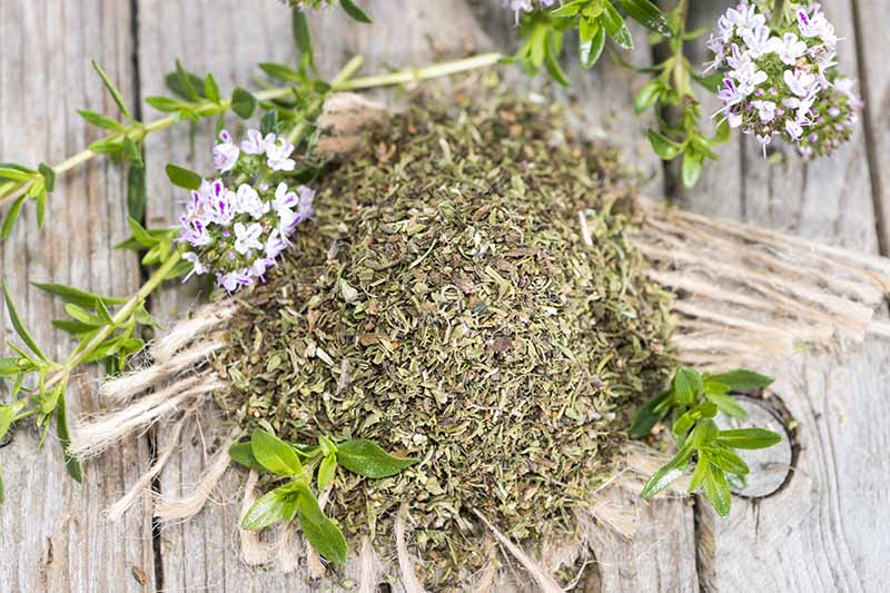 A top down close up picture of a pile of dried winter savory leaves, scattered with some fresh ones and some tiny pink and white flowers on a rustic mat. The background is a wooden table.