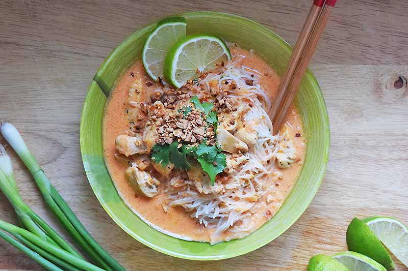 A top down picture of a green bowl with chicken and noodles in a creamy red curry sauce, topped with chopped nuts, cilantro, and slices of lime. To the right of the bowl are two wooden chopsticks, and lime slices. To the right of the bowl are some bunching onions. The background is a wooden surface.
