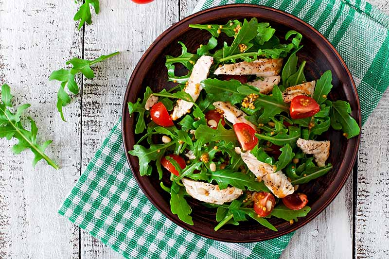 A top down close up picture of a salad of arugula, fresh cherry tomatoes and chicken, set on a green checked cloth on a wooden surface.