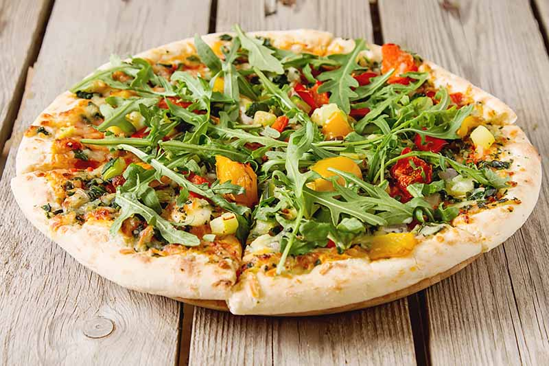 A close up of a pizza with fresh arugula on the top, set on a wooden table.