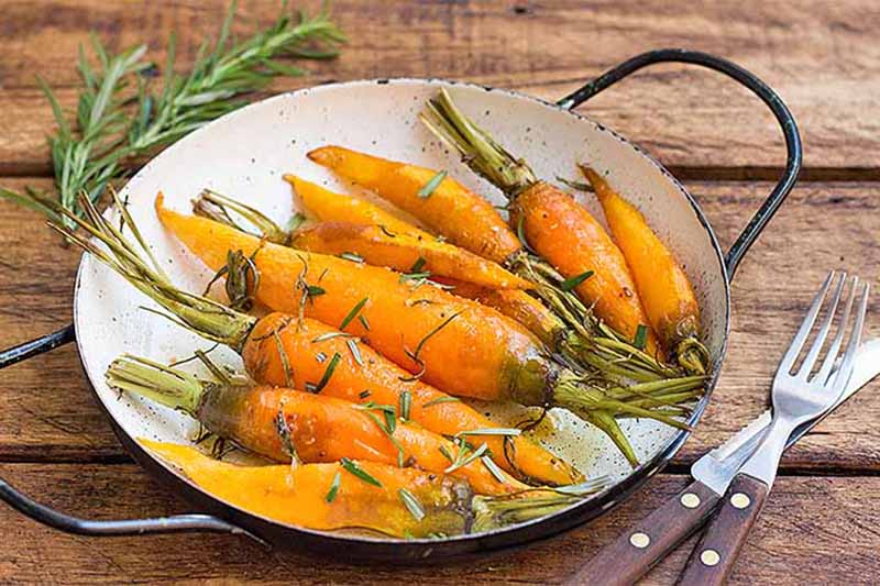 A cast iron skillet pictured on a rustic wooden surface containing fresh roasted carrots with rosemary. On the right is a knife and fork with wooden handles.