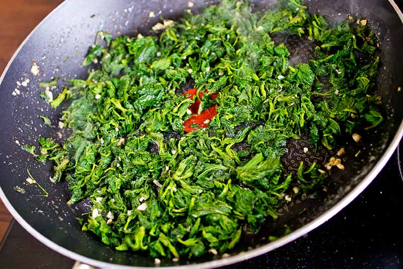 A close up of stinging nettle leaves being sauteed in a dark frying pan with garlic pieces.