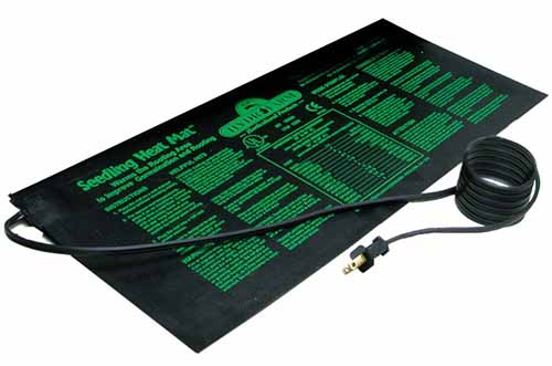 A close up of a black plastic heat mat with a electrical cord and plug. There is green writing on the pad.