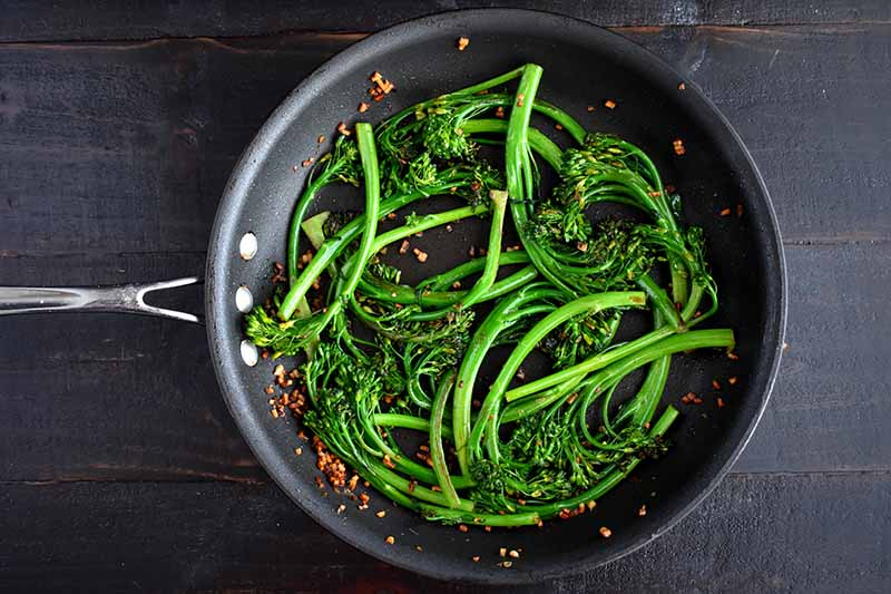 A close up top-down picture of a black frying pan with stir fried broccolini in garlic, set on a dark wooden surface.