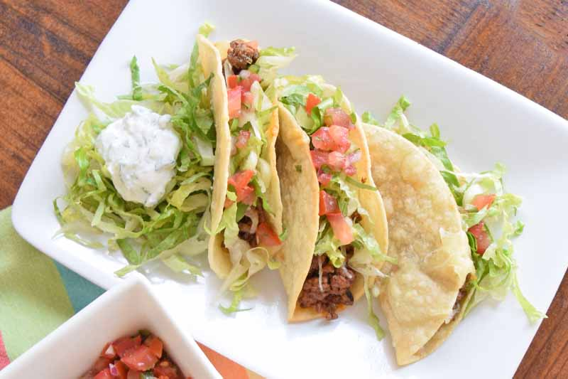 A top down close up of a white rectangular plate with beef tacos and iceberg lettuce set on a brown wooden surface.
