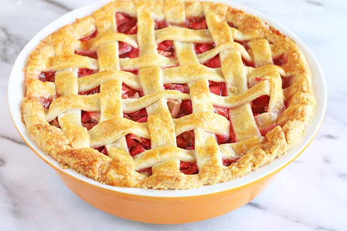 A close up of a freshly baked strawberry and rhubarb pie with a lattice pastry topping in an orange bowl set on a marble surface.