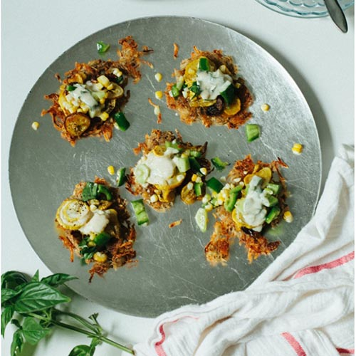 A top down picture of a silver plate with five freshly cooked fritters, topped with yoghurt and scattered with corn and green pepper, set on a white surface.