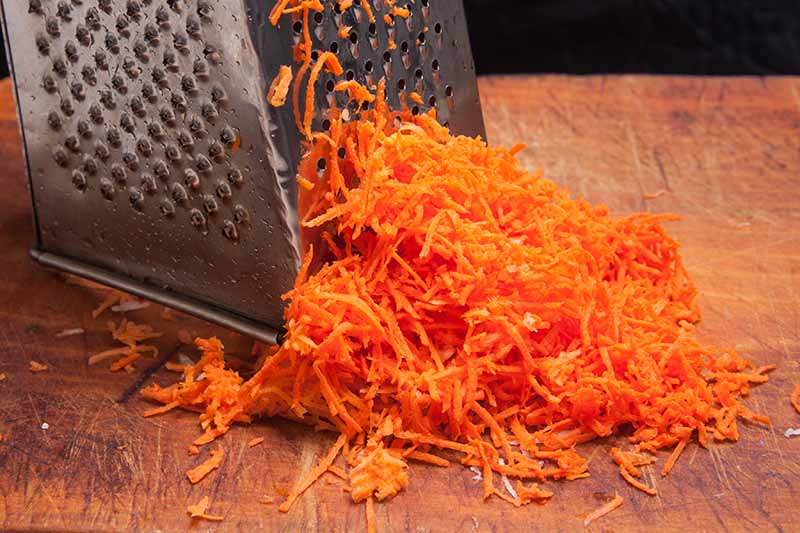 A close up of a cheese grater being used to grate carrots onto a wooden chopping board on a dark background.