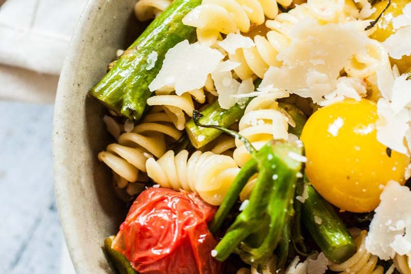 A close up of a rustic bowl of pasta salad with grilled tomatoes, broccolini, and parmesan cheese, set on a blue surface.