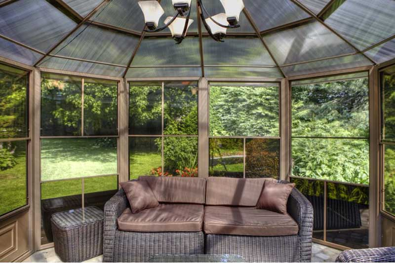 Interior view of a garden gazebo with mesh panels and polycarbonate roofing material, in an aluminum frame. There is a sofa and table set inside and a garden view through the windows,