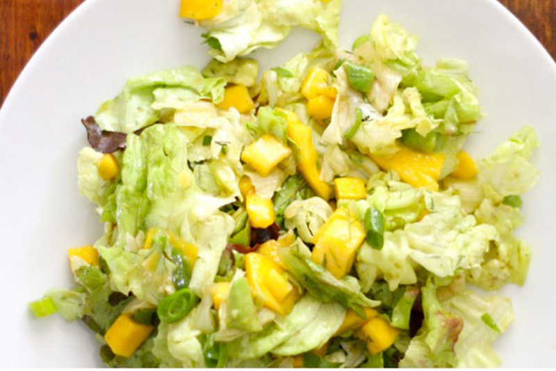 A top down close up picture of a white plate with a mango, avocado, and butterhead salad with tangy dressing set on a wooden surface.