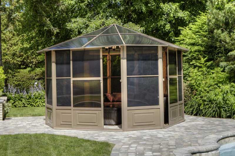 An aluminum-framed gazebo set on a stone surface next to a swimming pool, the sliding doors slightly open and garden scene in the background in bright sunshine.