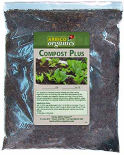 A close up of the packaging of a bag of compost with green and white labelling on a see-through bag.