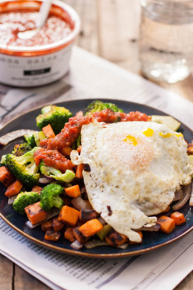 A vertical close up picture of a dark ceramic plate with a mixture of roasted vegetables topped with a fried egg and salsa, set on a newspaper with a bowl of salsa in the background in soft focus.