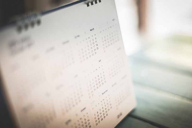 A calendar set on a wooden surface in soft focus.