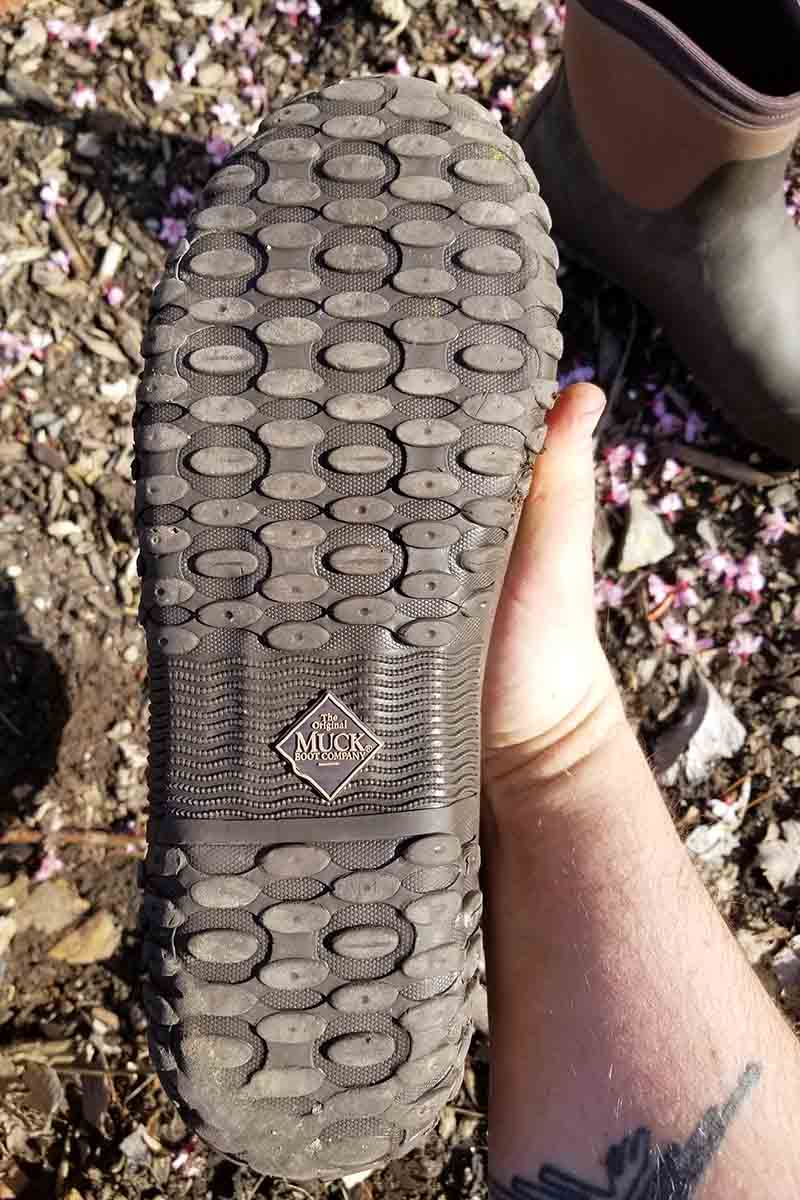 A close up vertical picture of the bottom of a Muckster II Ankle gardening shoe showing the tread.