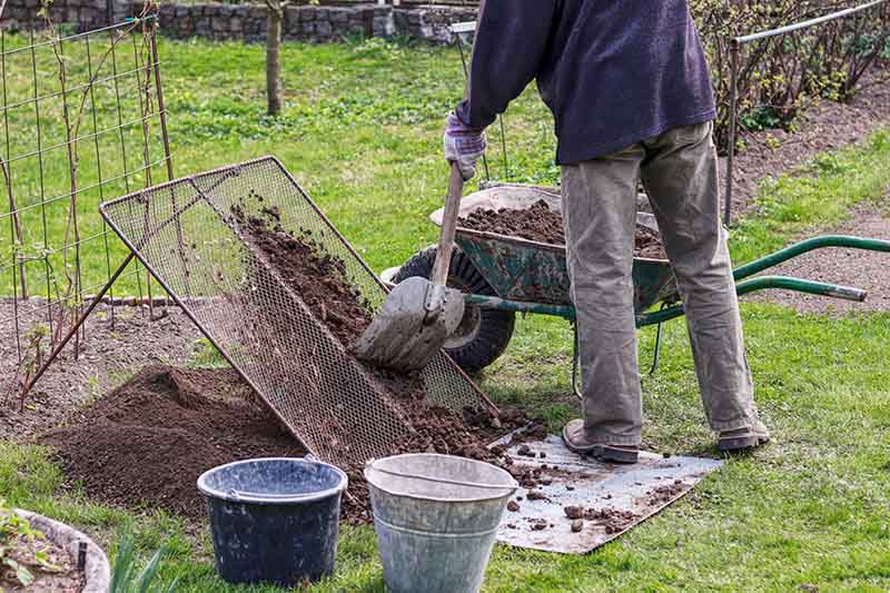 A man digging garden soil out of a wheelbarrow and sieving it through a metal grid to remove clumps and stones. In the background is a garden scene.