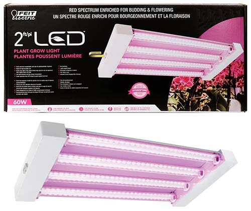A close up of the packaging of an LED grow light for indoor gardening. At the top of the frame is cardboard packaging and below it is the unit in white plastic with pink LED bulbs.