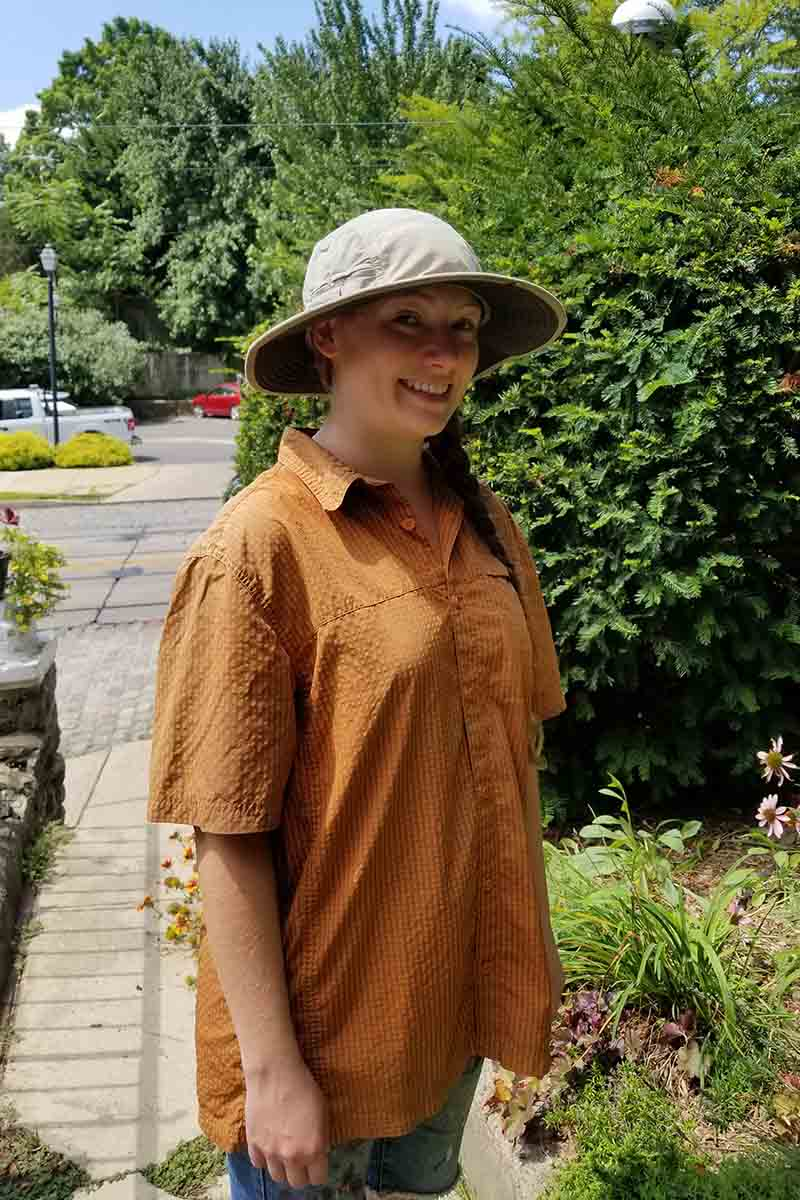 A close up of a gardener wearing sun protective clothes in the form of a wide brimmed hat and a loose, short sleeved shirt for working in the heat of summer.