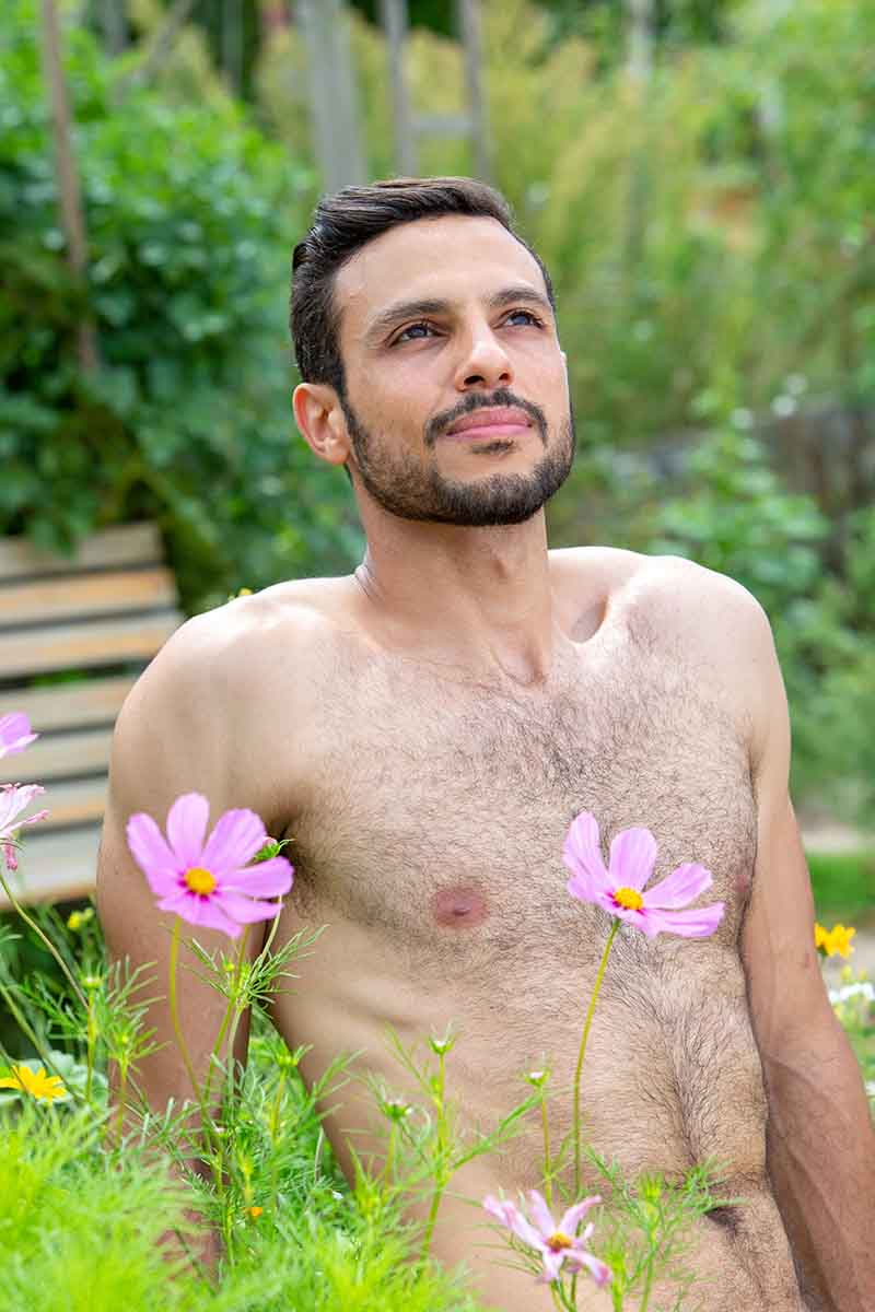 A vertical picture of a young man with a bare chest sitting in the garden with pink flowers in the foreground and soft focus background.