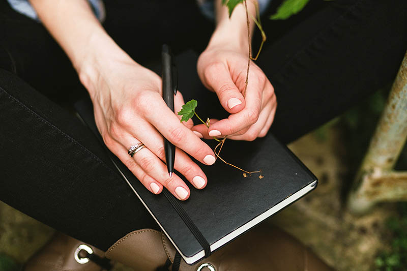 A close up of a woman sitting cross legged in the garden with a leather notebook and pen in one hand and a small vine in the other, on a soft focus background.