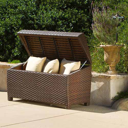A dark brown wicker deck storage box with the lid open containing three outdoor cushions, pictured in bright sunshine, with a low wall, a planter, and a garden scene in the background.