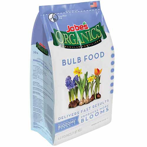 A close up of the packaging of a bulb food fertilizer with blue and white text and pictures of different flowering bulbs.