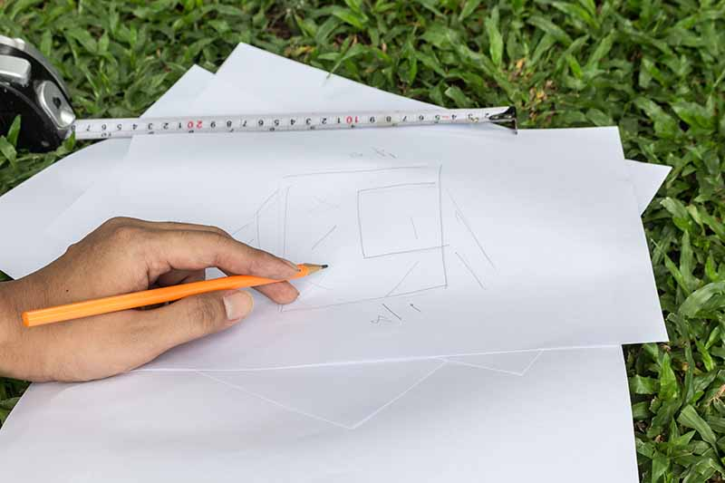 A hand from the right of the frame holding a pencil sketching a garden design on blank sheets of paper set on the lawn, with a measuring tape.