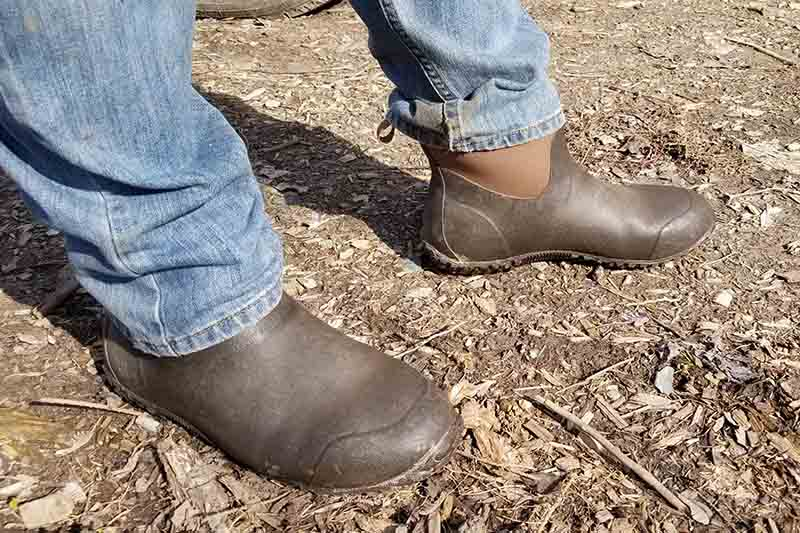 A close up of a man's feet wearing the Original Muck Boot Company's Muckster II Ankle gardening shoe, with a pair of jeans.
