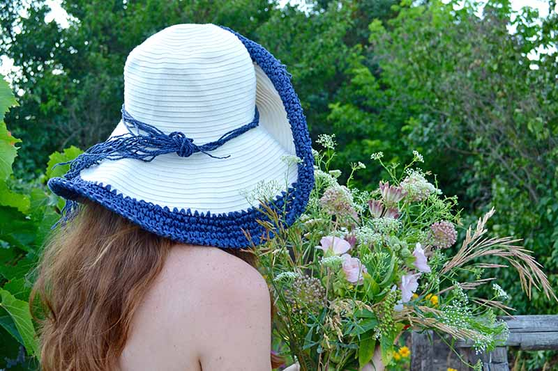 A close up of a young woman with bare shoulders wearing a blue and white hat holding a bunch of freshly picked flowers with trees in soft focus in the background.