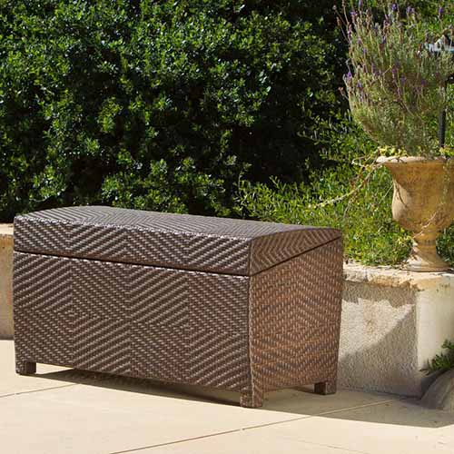 A dark brown wicker deck storage box pictured in bright sunshine set on a tiled surface with a small wall and planter in the background and a garden scene in soft focus.