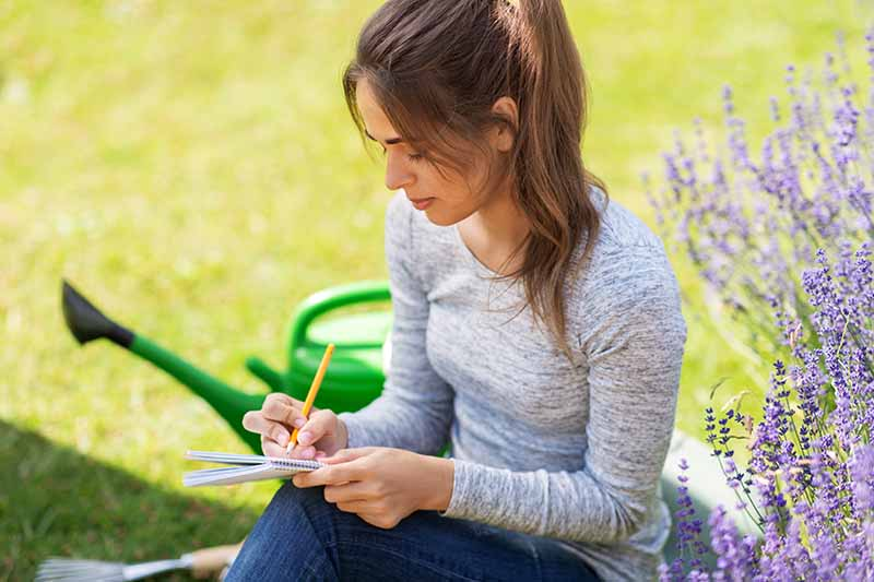 A woman sits in the garden holding a pen and writing in a notebook, with purple flowers to the right of the frame and a green watering can and lawn in soft focus in the background.