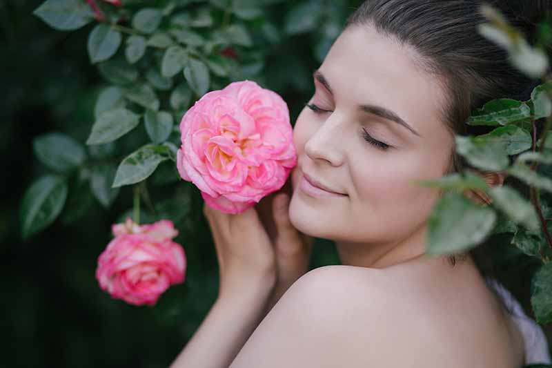 A close up of a young woman with bare shoulders, cupping a pink flower next to her face with her eyes closed, on a soft focus background.