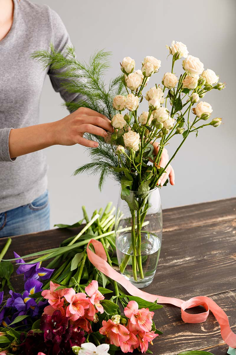 A vertical picture of a woman dressed in a gray sweater from the left of the frame arranges a glass vase with cut flowers, on a wooden surface and a white background.