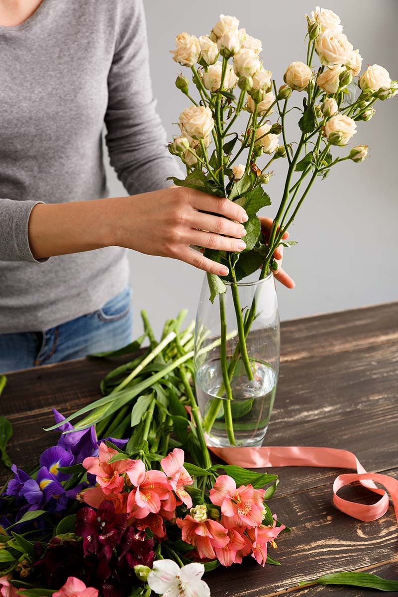 A vertical picture of a woman's hand from the left of the frame arranges white roses in a glass vase set on a wooden surface. To the left of the vase are red and purple flowers.