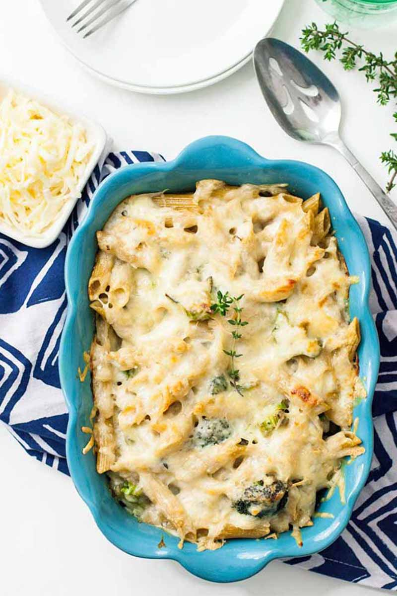A close up top down vertical picture of a blue casserole dish with a pasta and broccoli bake set on a blue and white fabric with a small bowl of cheese to the left.
