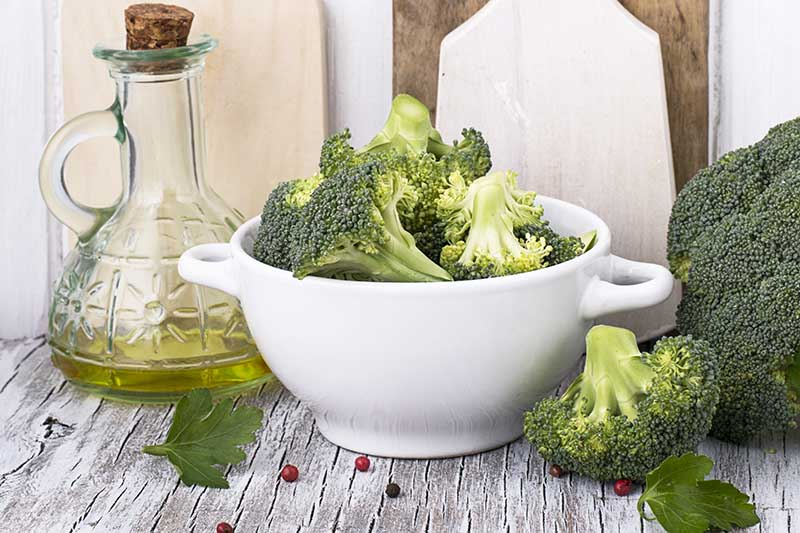 A close up of a white ceramic bowl with fresh florets of Brassica oleracea var italica set on a wooden surface. To the left of the frame is a glass bottle containing olive oil.