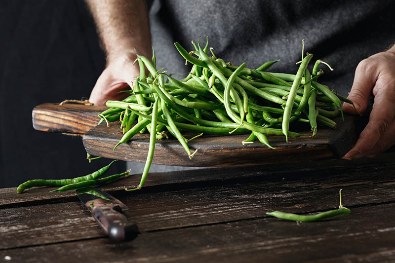 A close up of a man holding a wooden chopping board with a fresh harvest of green bush beans and a knife in the foreground.