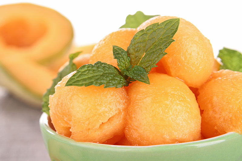 A close up of a cantaloupe made into circular balls set in a green bowl with mint as a garnish on a soft focus background.