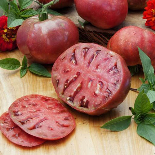 A close up of a sliced 'Cherokee Purple' tomato, surrounded by herbs and set on a wooden surface.