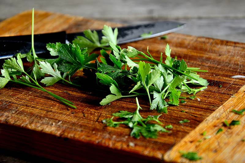 A close up of fresh parsley set on a wooden chopping board with a knife in soft focus in the background.
