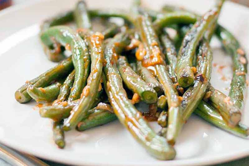 A close up of a white plate with garlic roasted green beans on a soft focus background.