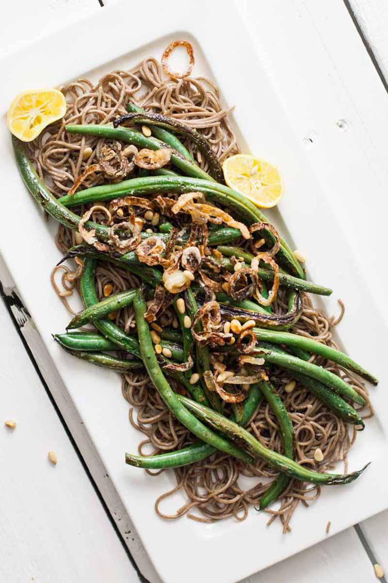 A close up vertical picture of a rectangular white plate with green beans and soba noodles topped with pine nuts and caramelized onion. To the side of the plate is lemon sections.