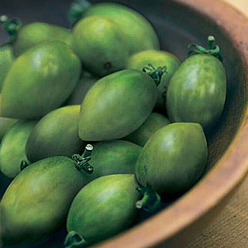 A close up of a wooden bowl containing 'Green Envy' fruits.