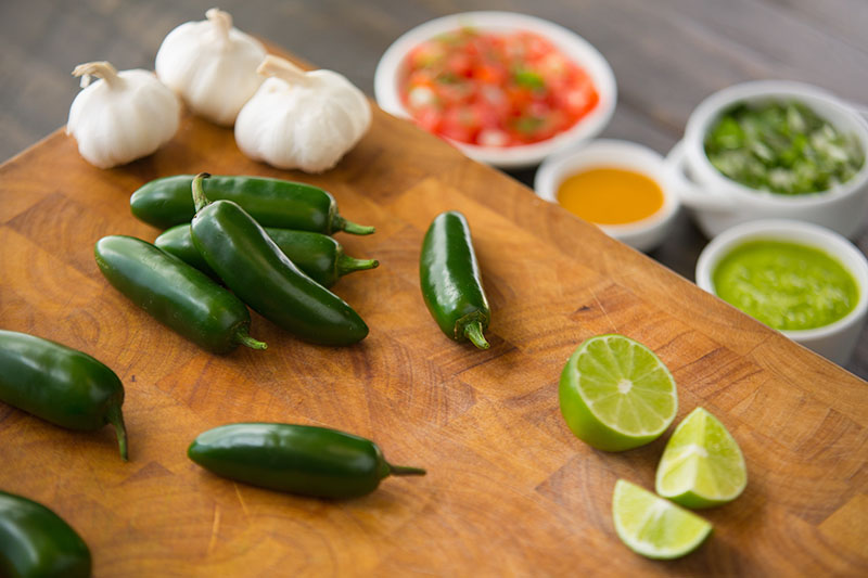 A close up of a wooden chopping board with sliced lime, 'Jalapeno' peppers, and garlic. In the background is condiments in white ceramic pots in soft focus.
