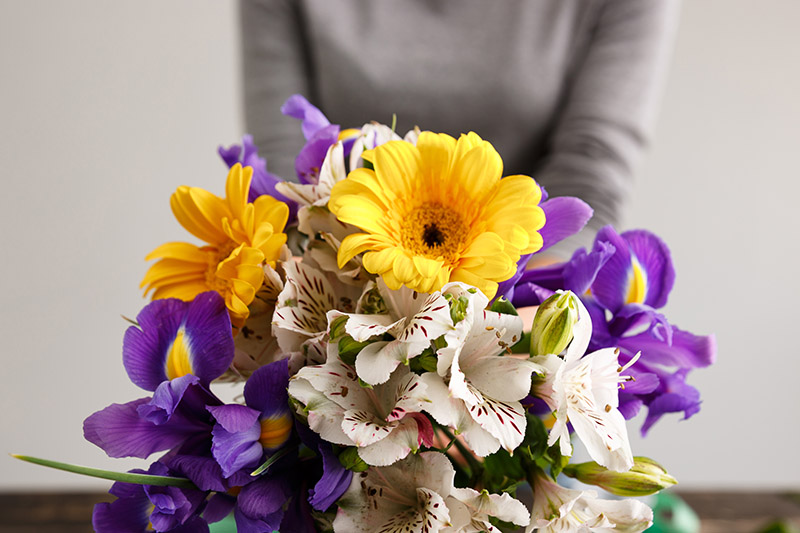 A close up of a fresh bouquet of cut flowers with a woman in a gray sweater in soft focus in the background.