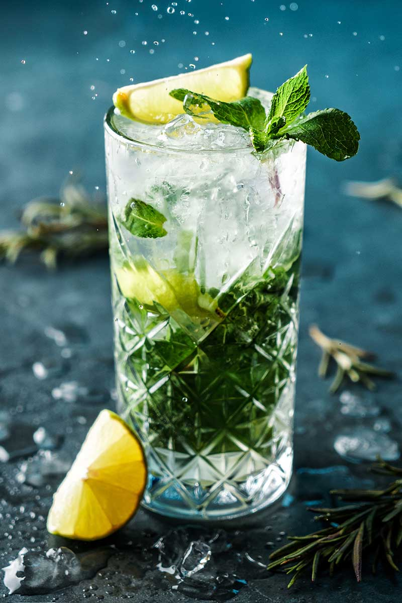 A close up vertical picture of a tall glass with a drink containing mint and lemon with water droplets and herbs on a soft focus blue surface.