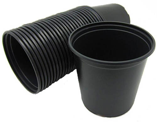 A close up of a selection of black plastic nursery pots with one standing upright and several stacked, on a white background.